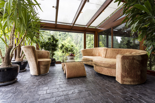 Comfortable plush lounge set in a conservatory with dark stone floor