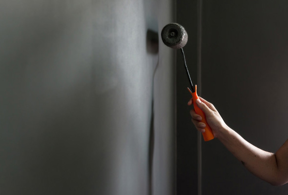 In the dark mood, Hand holding paint roller applying grey paint on wall. Copy space.